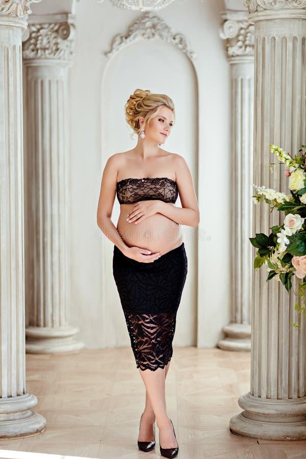 黑裙子和鞋带上面的美丽的怀孕的金发碧眼的女人保留Th 库存照片