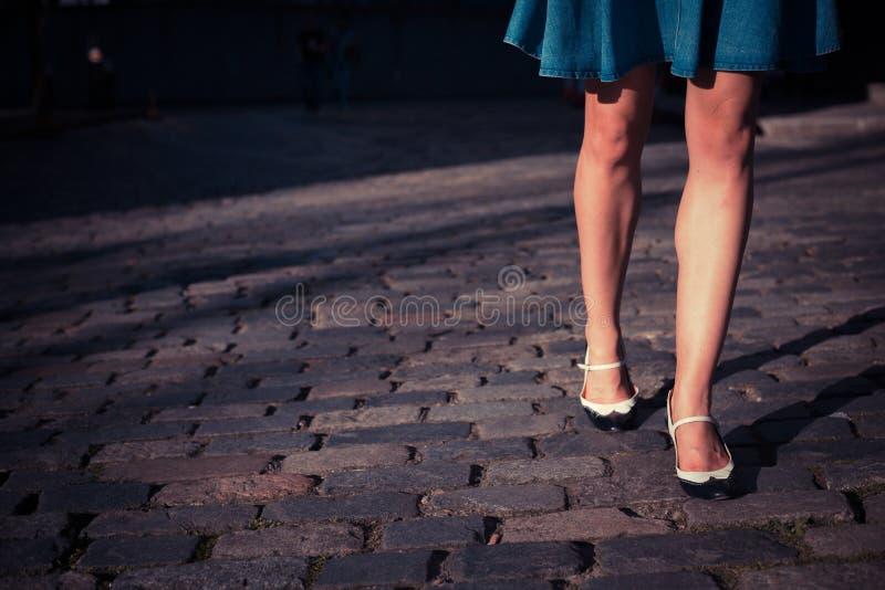 裙子的少妇走在一条被修补的街道上的 库存照片