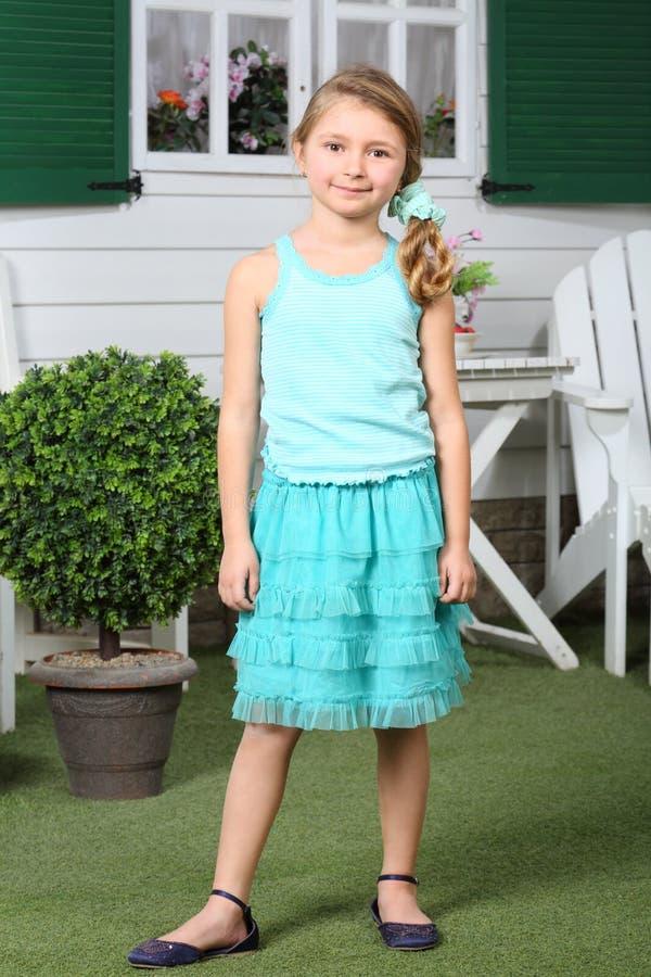 裙子的愉快的矮小的逗人喜爱的女孩站立近的村庄。 库存照片