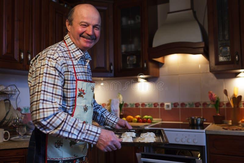 围裙的一个年长人在家准备饼 免版税库存照片