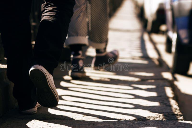 裤子和运动鞋的两个人走在石路面的 库存图片