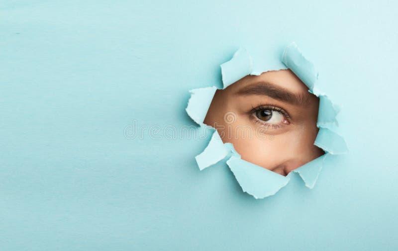 裸体构成 与看通过被撕毁的蓝纸的染睫毛油的女性眼睛 库存图片