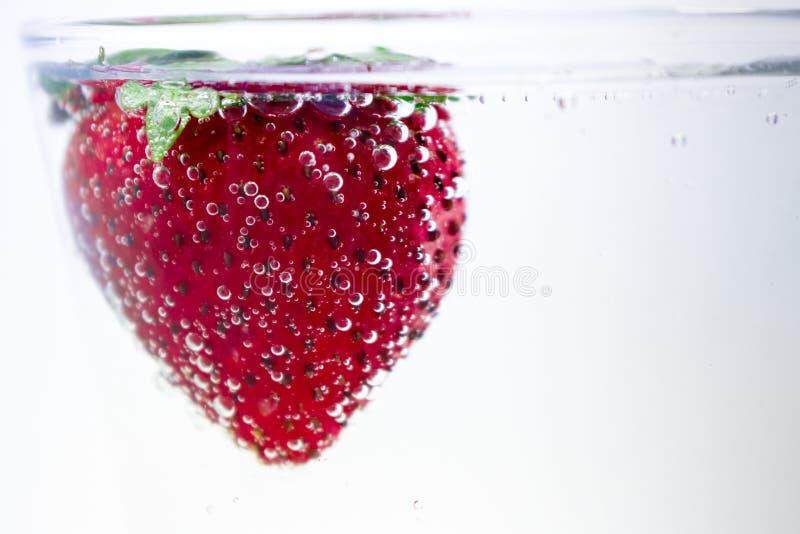 裸体游泳在泡沫腾涌的水中的草莓 免版税库存照片