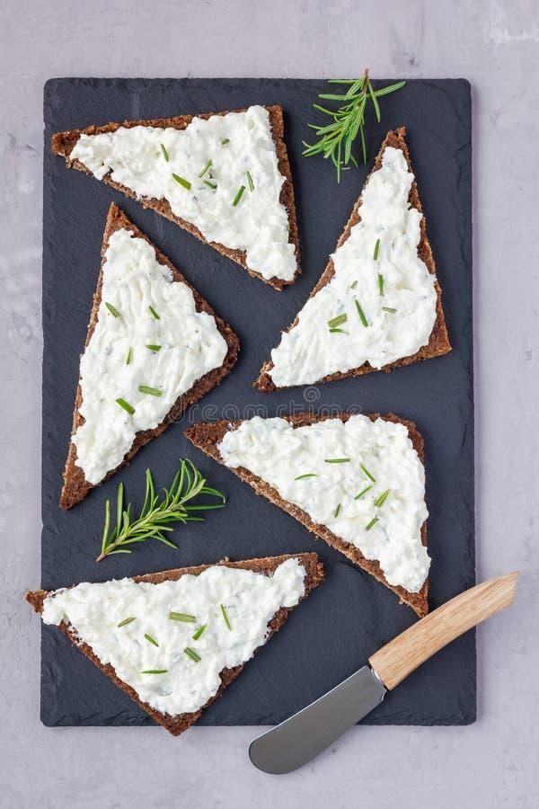 裸麦粉粗面包面包用希脂乳,乳脂干酪、迷迭香、柠檬和大蒜在板岩板浸洗,顶视图,垂直 免版税库存照片