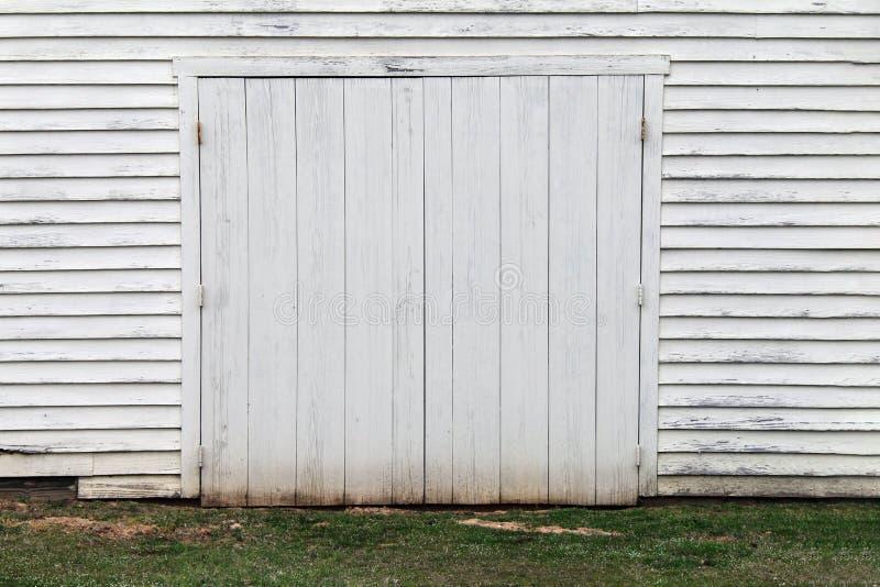 褪色的白色木质仓库门草 图库摄影