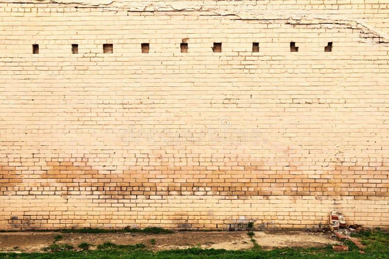 褪色的风化石砖仓墙 库存照片