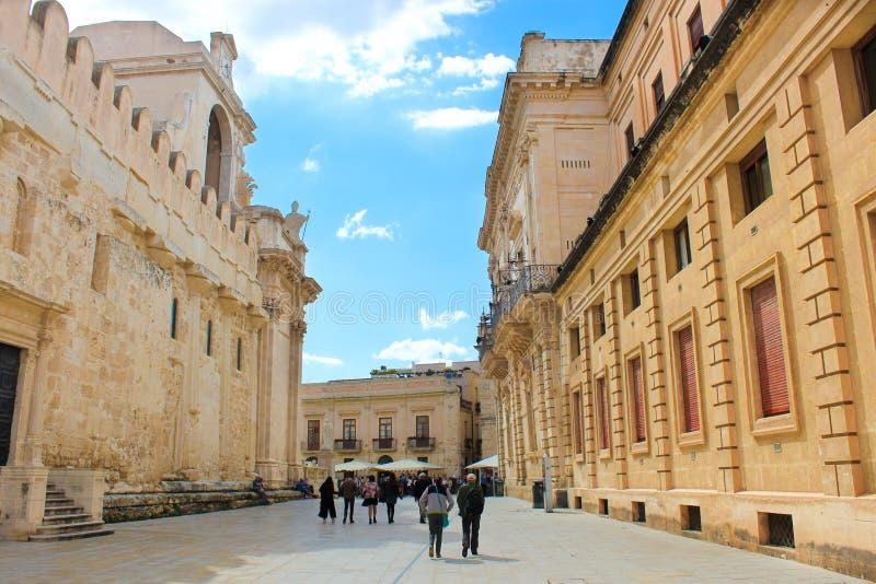 西勒鸠斯,意大利- 2019年4月10日:走到沿西勒鸠斯美丽的天主教大教堂的广场中央寺院正方形的人们  库存图片