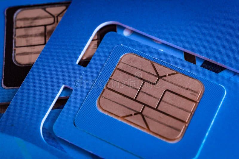西姆卡片使用宏观射击的流动聪明的电话关闭在蓝色 免版税库存图片