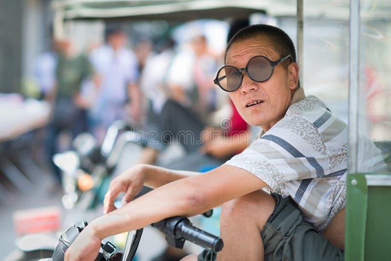 西安,陕西,中国- 08 11 2016年:一个中国人的画象有葡萄酒圆的太阳镜的在一tuk tuk在西安,中国 库存图片