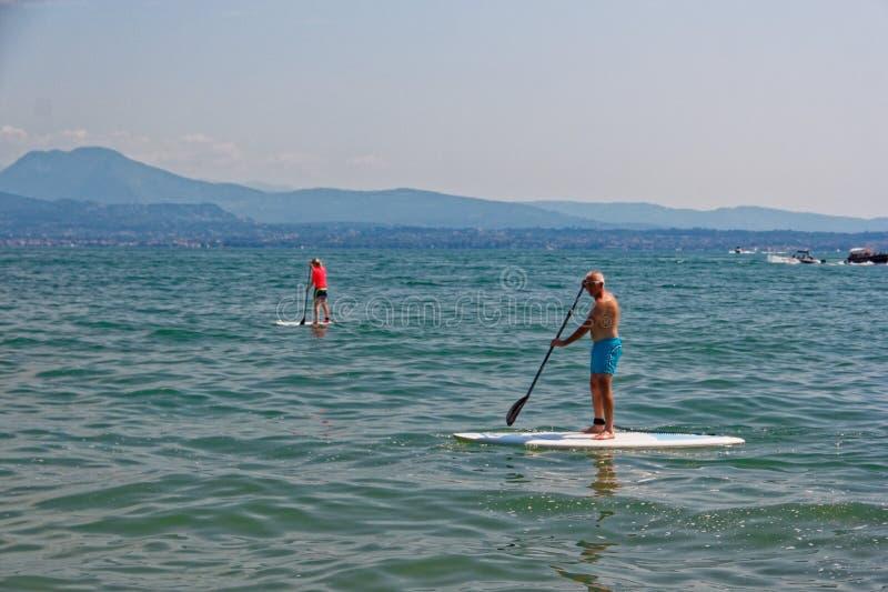 西尔苗内,意大利2018年8月17日:加尔达湖 冲浪板的人们 库存图片