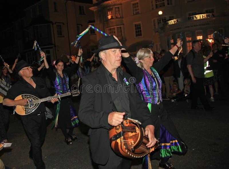 西德茅斯,德文郡,英国- 2012年8月10日:一个小组音乐家和在淡紫色和绿色打扮的障碍物舞蹈家参加 库存照片