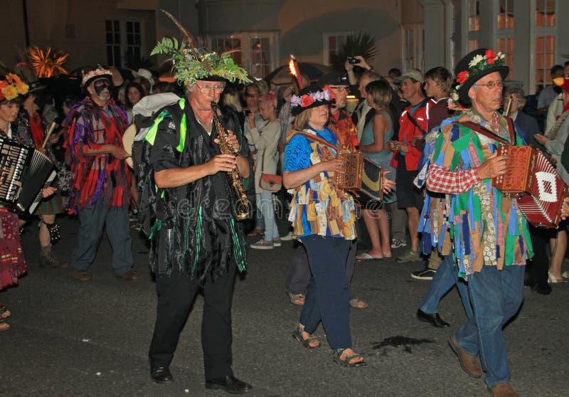 西德茅斯,德文郡,英国- 2012年8月10日:在开花的帽子打扮的一个小组音乐家和褴褛背心参加 免版税库存照片