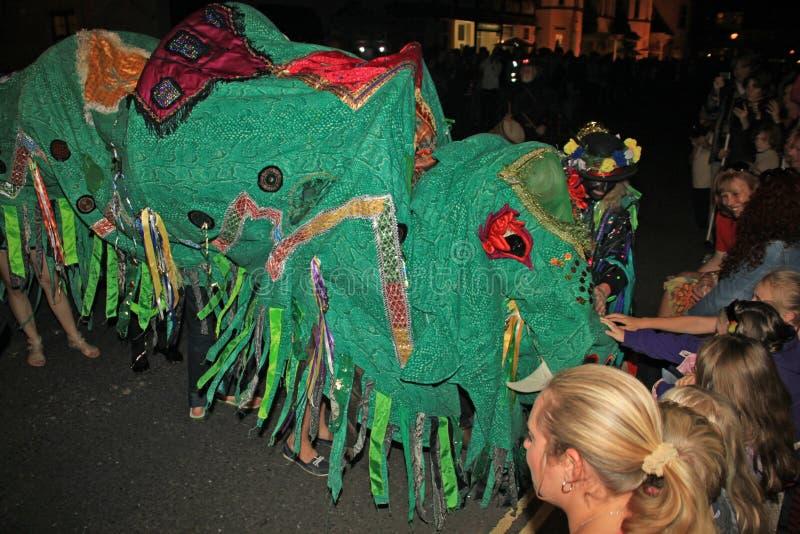 西德茅斯,德文郡,英国- 2012年8月10日:当它参加夜间,一条绿色中国龙得到抚摸由观众 免版税库存照片