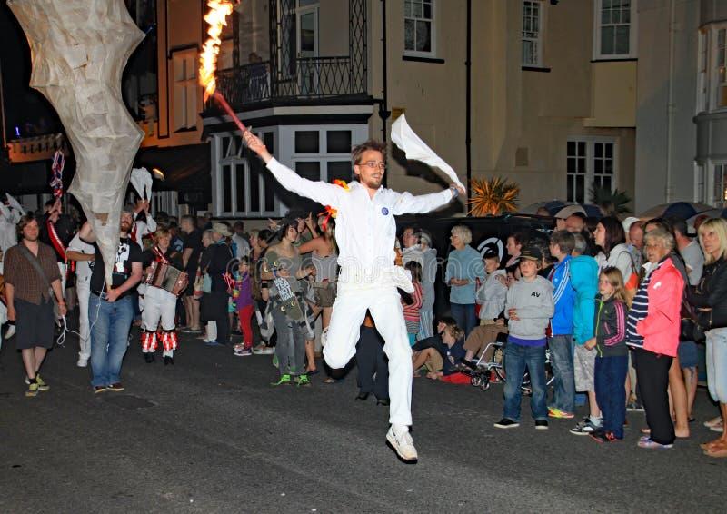 西德茅斯,德文郡,英国- 2012年8月10日:所有在白色和举行布料和发火焰打扮的一非常精力充沛的年轻人 免版税图库摄影