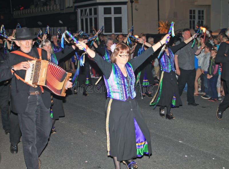 西德茅斯,德文郡,英国- 2012年8月10日:在淡紫色和绿色和对负和障碍物舞蹈家打扮的一个小组音乐家他们 图库摄影