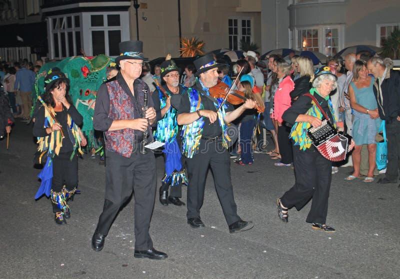 西德茅斯,德文郡,英国- 2012年8月10日:在装饰的高顶丝质礼帽打扮的一个小组音乐家和褴褛蓝色背心采取 库存图片