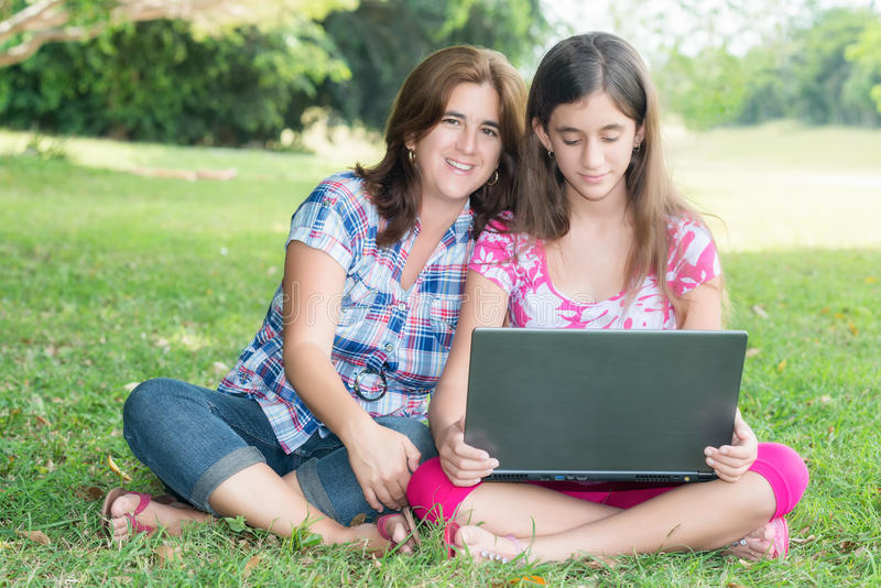 西班牙使用便携式计算机的女孩和她的年轻母亲胜过 库存照片
