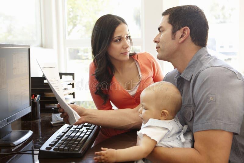 西班牙夫妇和婴孩在家庭办公室 库存照片
