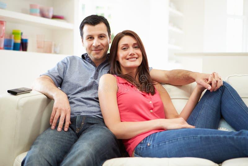 西班牙夫妇坐的观看的电视一起 库存图片