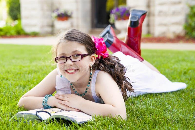 年轻西班牙女孩读书外部微笑 免版税库存照片