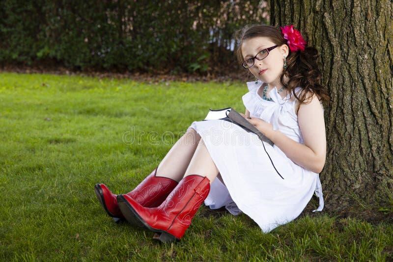 年轻西班牙女孩读在树下 免版税图库摄影