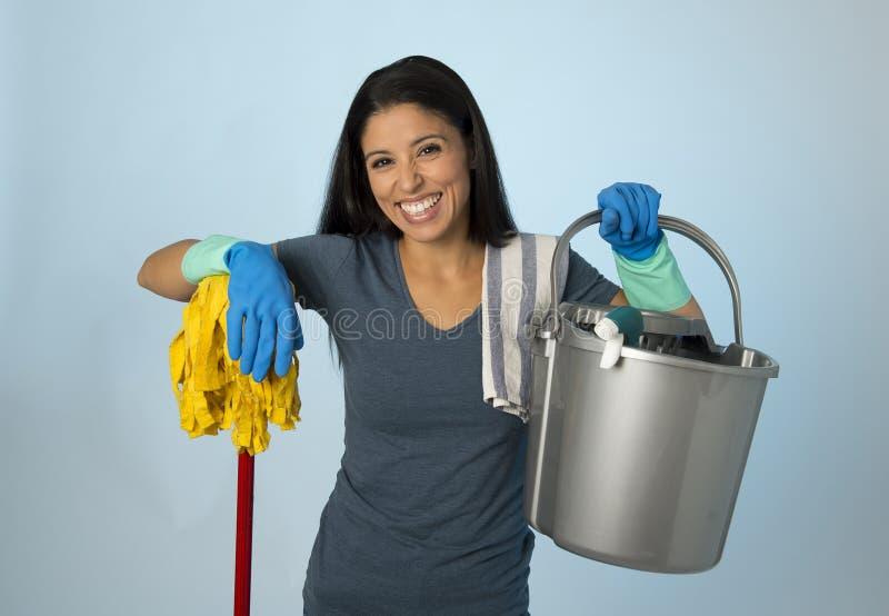 西班牙妇女愉快骄傲作为在家或旅馆佣人清洁和家务藏品拖把和洗涤物用桶提微笑 免版税库存图片