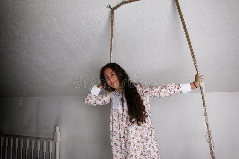 年轻西班牙妇女画象一件女睡袍的在摇摆 免版税库存照片