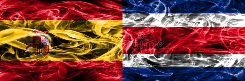 西班牙对哥斯达黎加肩并肩被安置的烟旗子 厚实的颜色 图库摄影