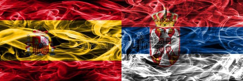 西班牙对塞尔维亚肩并肩被安置的烟旗子 重色的s 库存照片