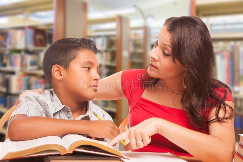 西班牙年轻学习在图书馆的男孩和女性成人 图库摄影