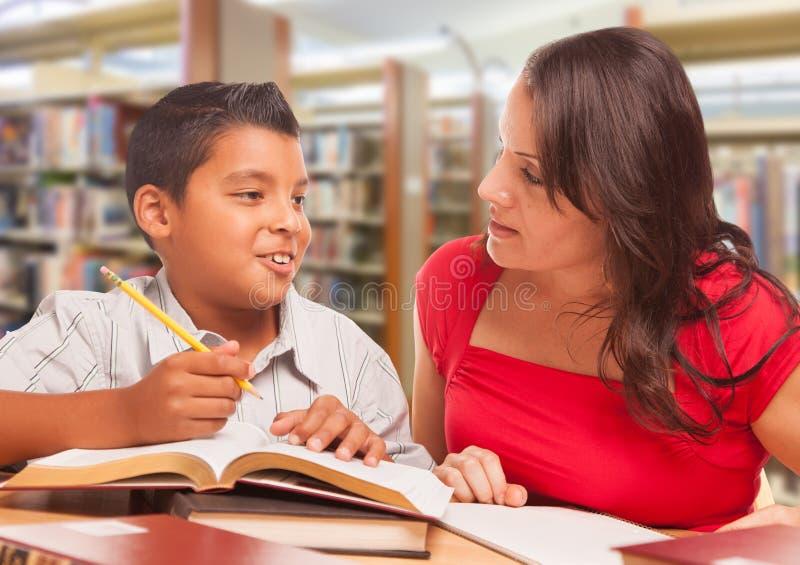 西班牙年轻男孩和学习在图书馆的Famle成人 免版税库存图片