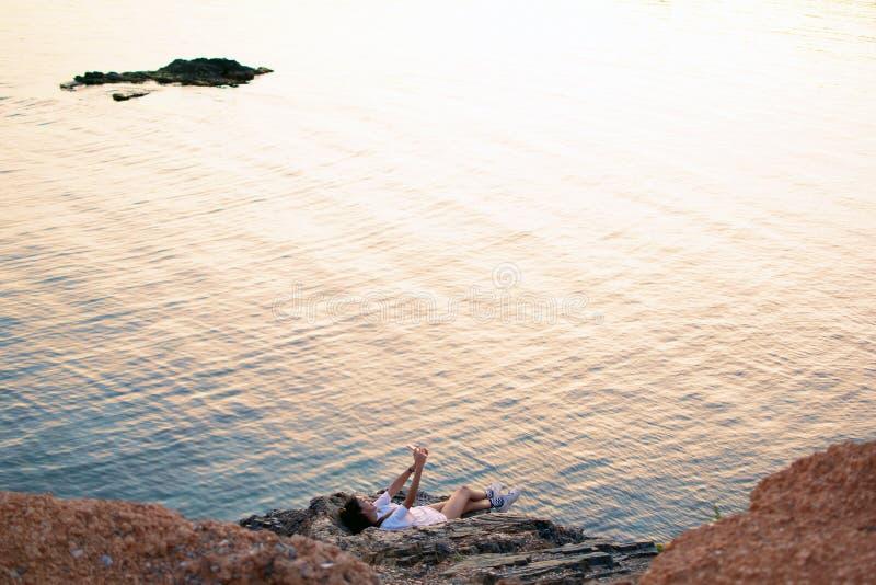 西班牙年轻美女在日落海滩用手机自拍 库存照片