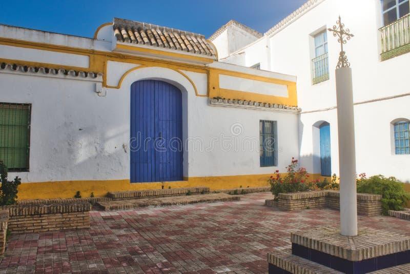 西班牙明亮地色的庭院在阳光下有在专栏的一个华丽十字架的 免版税库存图片