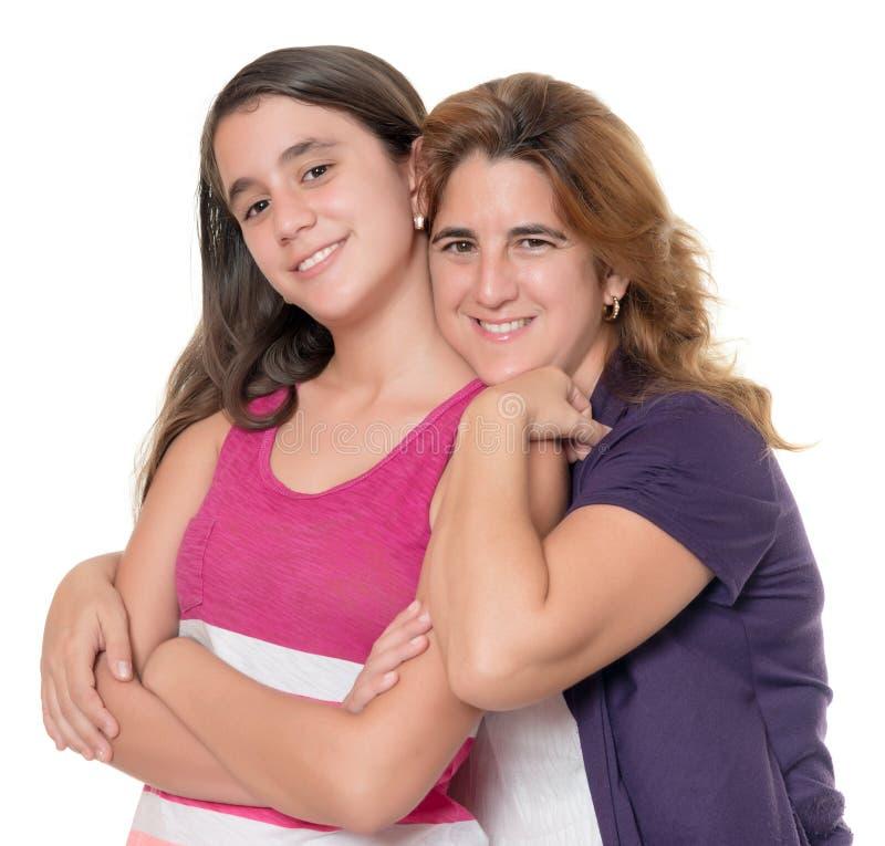 西班牙母亲拥抱在白色隔绝的她的十几岁的女儿 库存照片