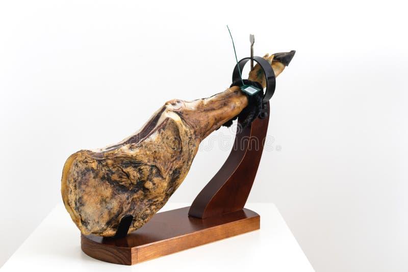 西班牙熟食干被治疗的肉火腿,整个腿,jamon在jamonero立场选择聚焦-白色背景的iberico bellota 免版税库存图片