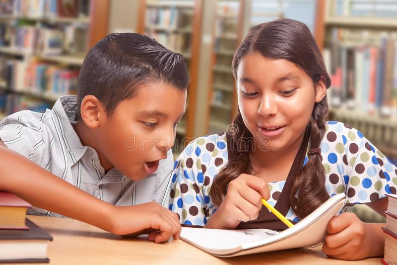 西班牙男孩和女孩获得一起学习的乐趣在图书馆 库存图片