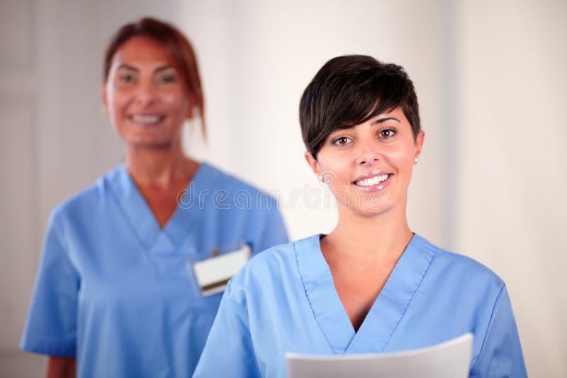 年轻西班牙的护士拿着文件 免版税库存图片