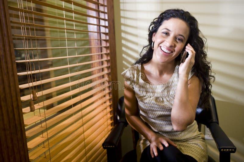 西班牙移动电话俏丽的联系的妇女 免版税库存照片