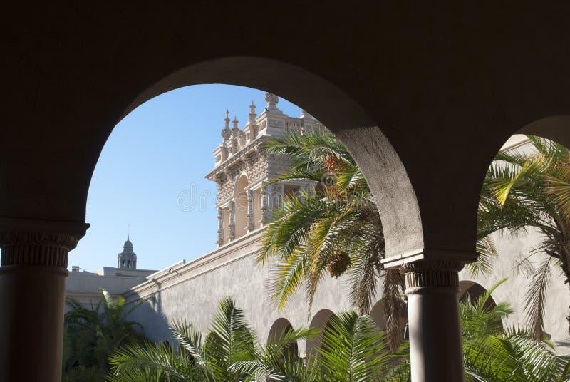 西班牙结构 看法通过宫殿的曲拱 在棕榈上在一好日子从事园艺 图库摄影