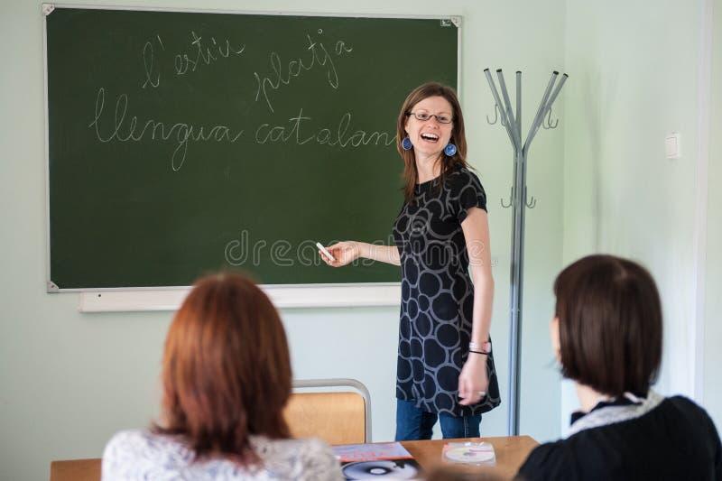 西班牙老师,黑板的年轻可爱的女孩解释学习材料 库存照片