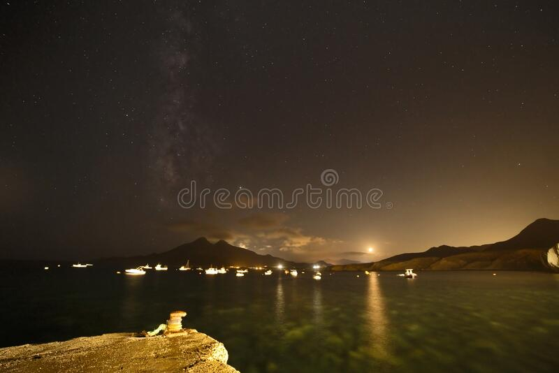 西班牙阿尔梅里亚Isleta del Moro码头的银河、满月和海中倒影 免版税图库摄影