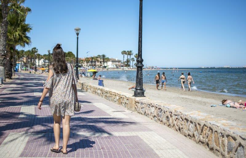 西班牙,穆尔西亚- 2019年6月22日:穿便服的愉快的年轻女人走在海滩 免版税库存照片