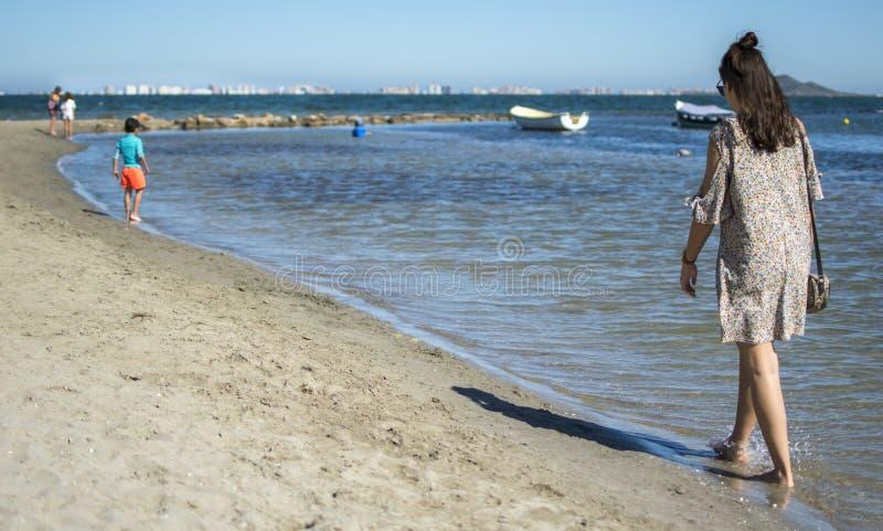 西班牙,穆尔西亚- 2019年6月22日:穿便服的愉快的年轻女人走在海滩 库存照片