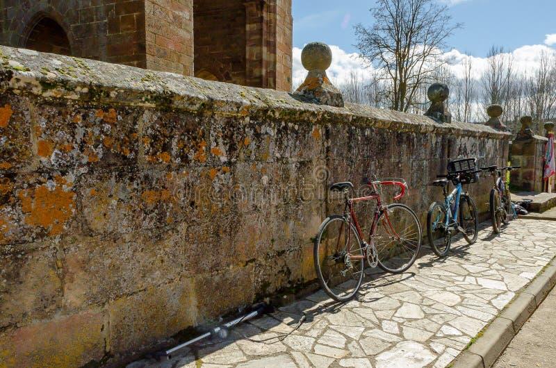 西班牙 在墙壁上停放的自行车萨利纳斯德皮苏埃尔加教会  帕伦西亚2013年3月 库存图片