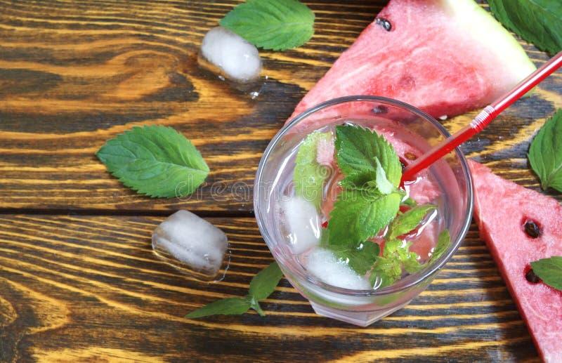 西瓜、绿色薄菏和冰水夏天刷新的鸡尾酒在木背景在一块玻璃与霜 免版税库存照片