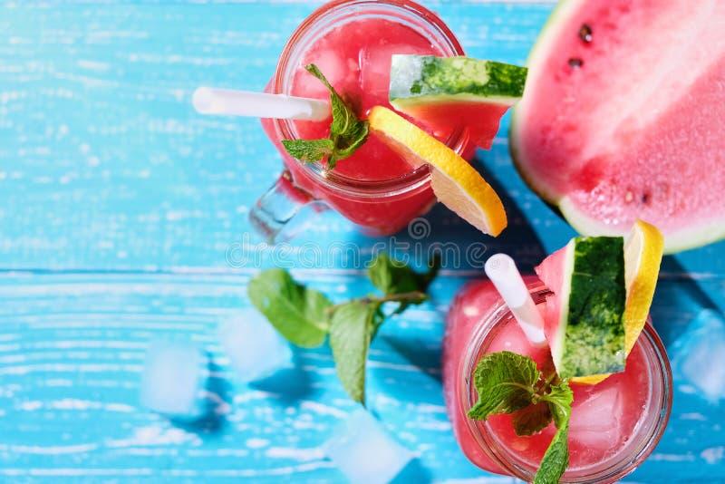 西瓜与冰和薄荷叶的夏天鸡尾酒 在淡色蓝色木背景的冷的茶点饮料 免版税库存照片