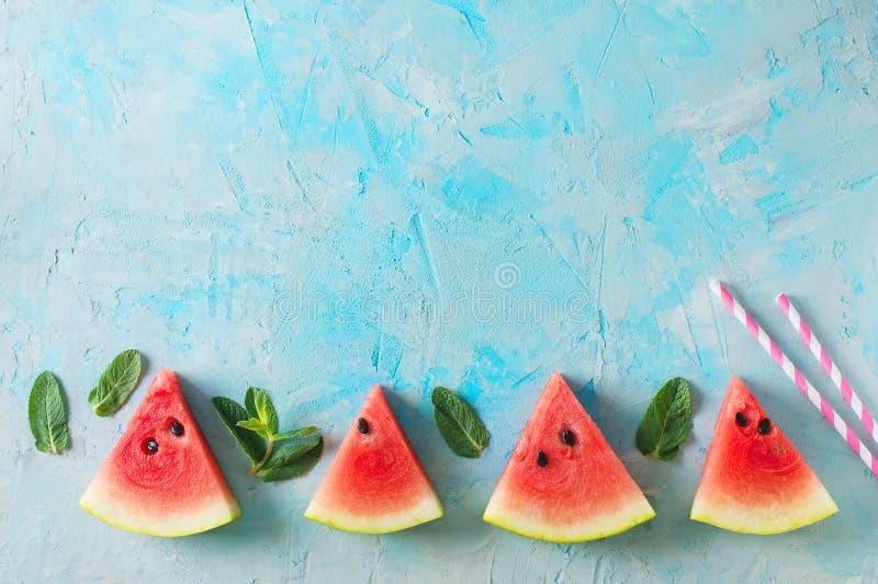 西瓜切片和薄菏框架在蓝色纹理 库存照片