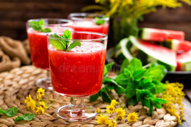 西瓜圆滑的人 西瓜饮料,在木土气背景的鸡尾酒 免版税库存照片