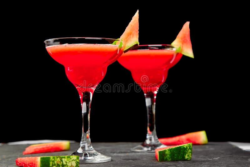 西瓜在黑背景的玛格丽塔酒鸡尾酒 新鲜的西瓜柠檬水用薄菏和冰为夏天集会 刷新 库存图片