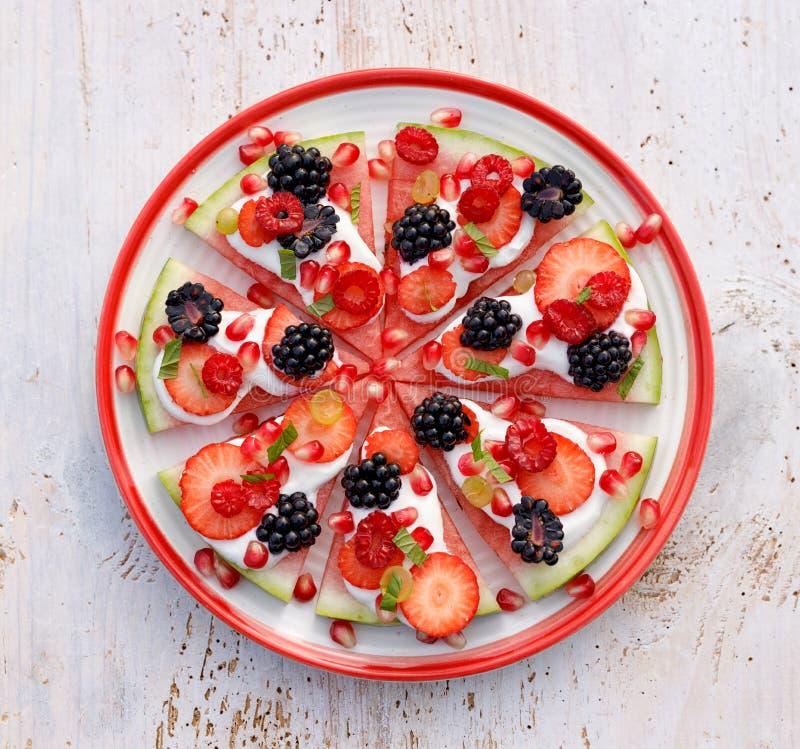 西瓜比萨、素食主义者、果子比萨用乳脂状的自然酸奶和新鲜水果在一块板材,在一张白色木桌上,顶面v 图库摄影